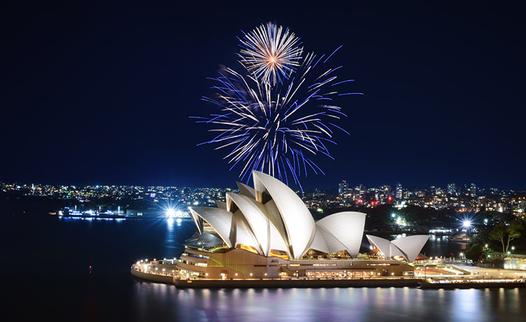Fireworks exploding in the night sky over the Sydney Opera House.