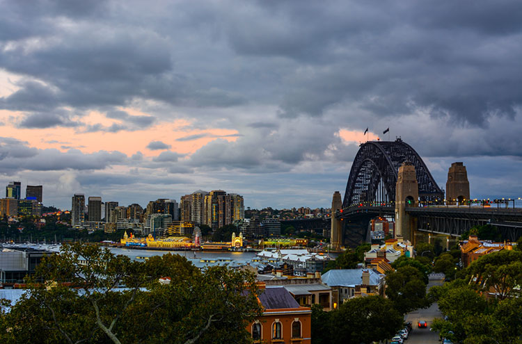 Sydney Harbour Bridge and waterfront with warm evening colors.