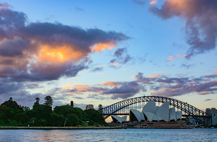 Sunset over Sydney Harbour and the city's iconic landmarks.