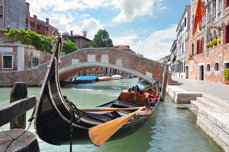 Venetian bridge over a canal with a gondola moored at the side.