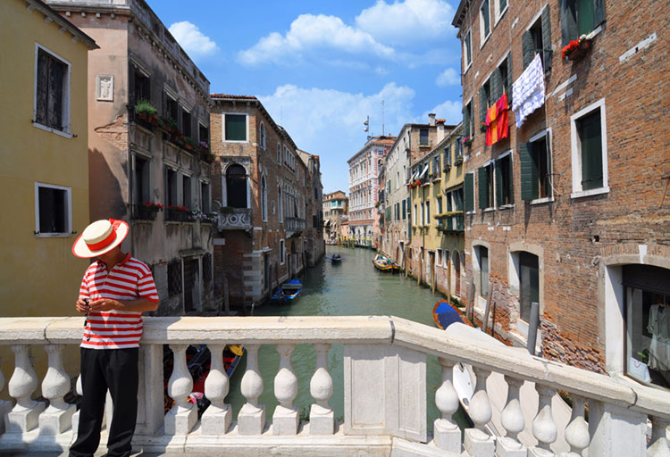 View of a Venetian canal with a gondolier dressed in traditional outfit.