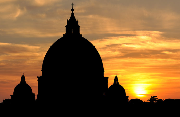 Orange sunset contrasting the darkened domes of St. Peter's Basilica.