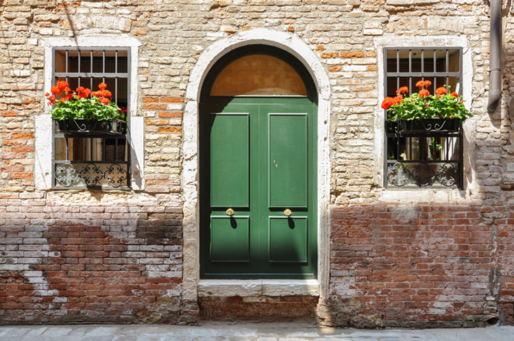 Geranium flower boxes and green doors on a cute home in Venice.