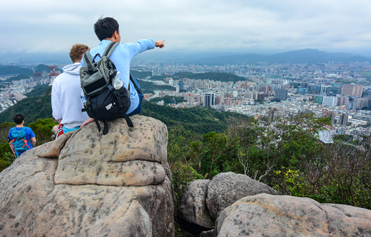 Young foreign student and Taiwanese man on a mountain overlooking Taipei.